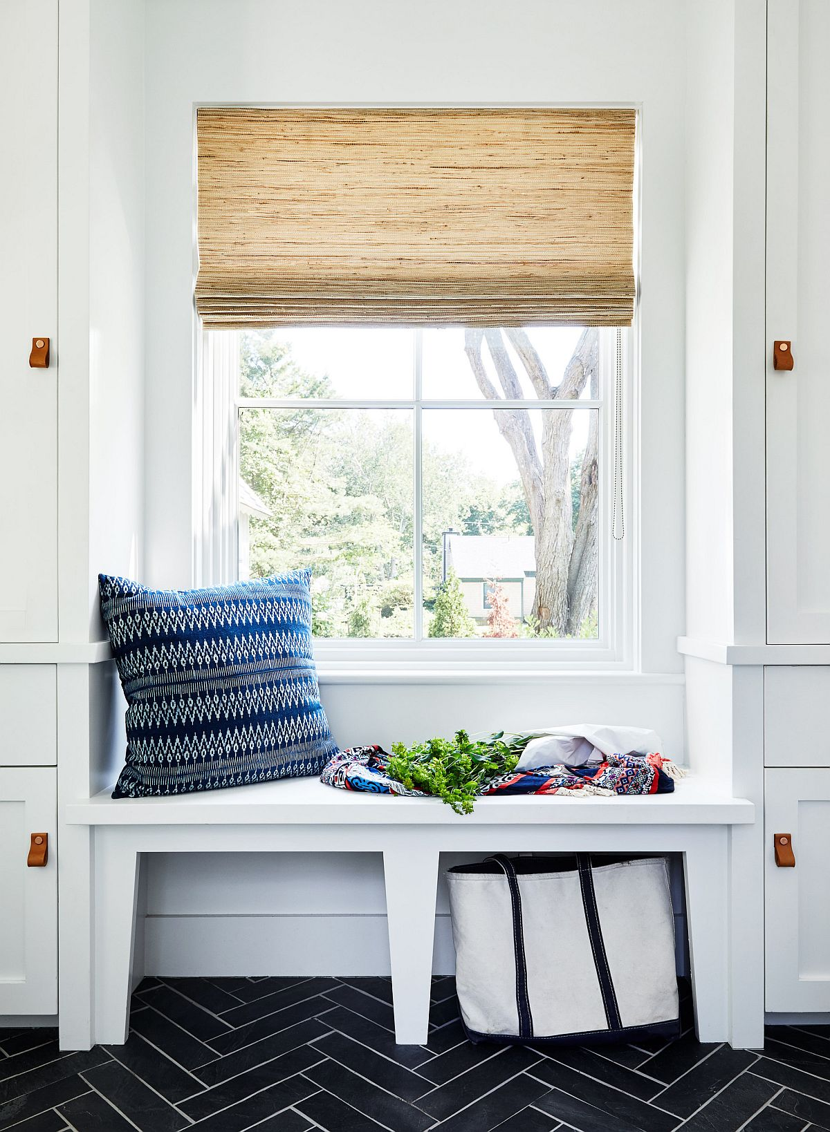 Tiny mudroom and entry with a small window seat and a bright blue throw pillow