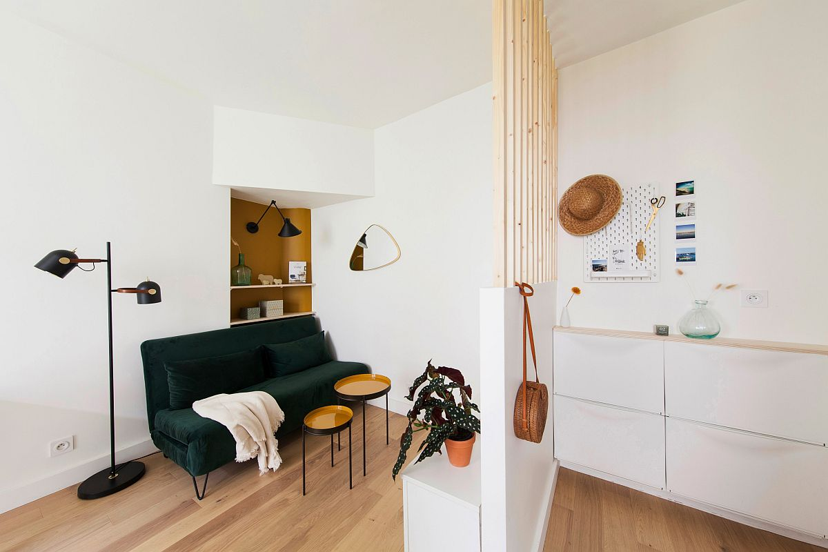 Tiny open living area of the Scandinavian style home with dark green sofa that seats two
