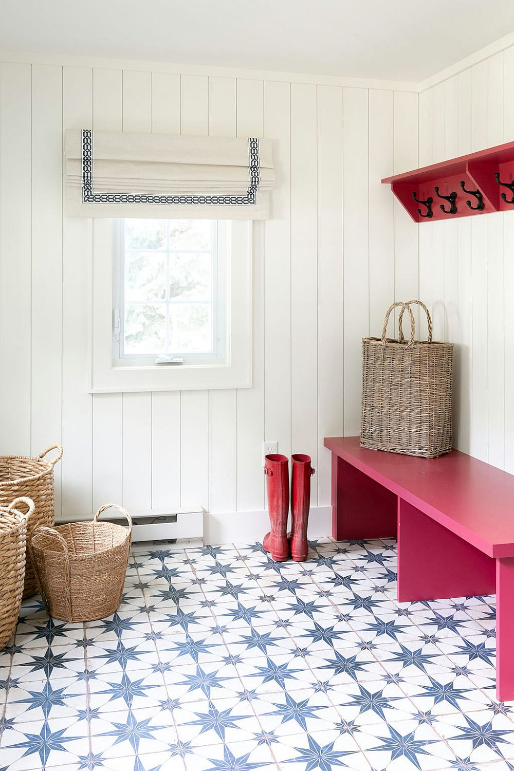 White mudroom with beach and cottage styles features patterned floor tiles and bright pink bench