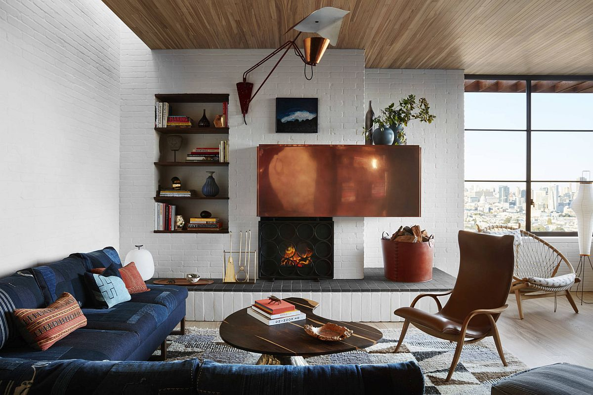Whitewashed brick walls coupled with lovely wooden ceiling and large glass windows inside the modern living room