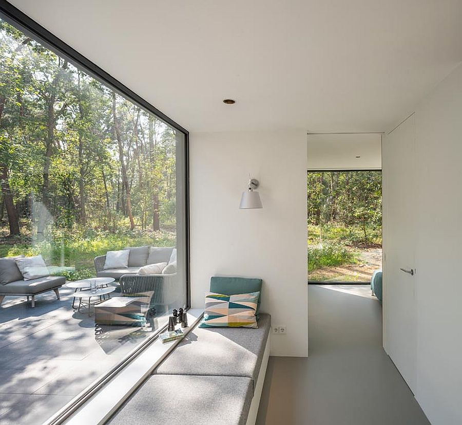 Window seat next to the large window allows those inside to enjoy the green landscape outside