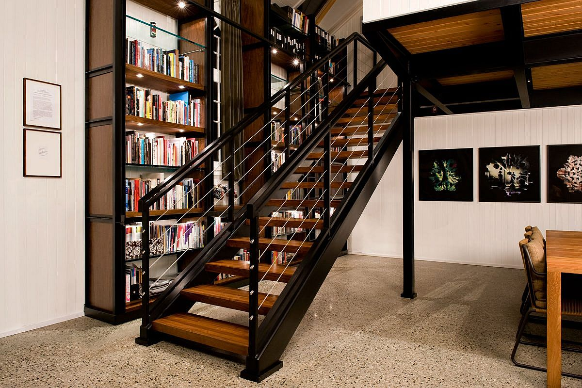 Wood and metal help create the beautiful staircase and bookshelf inside the church converted into loft