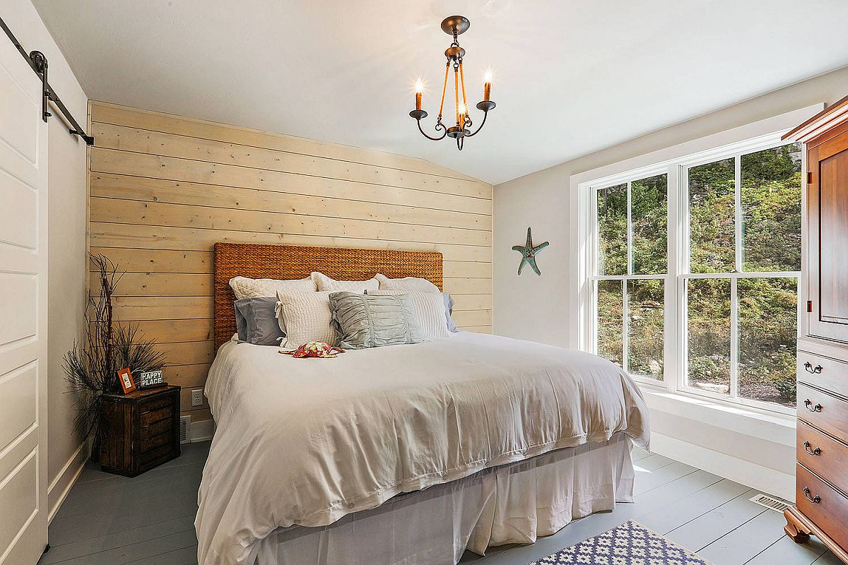 Wooden floor painted gray gives the modest beach style bedroom a more sophisticated look