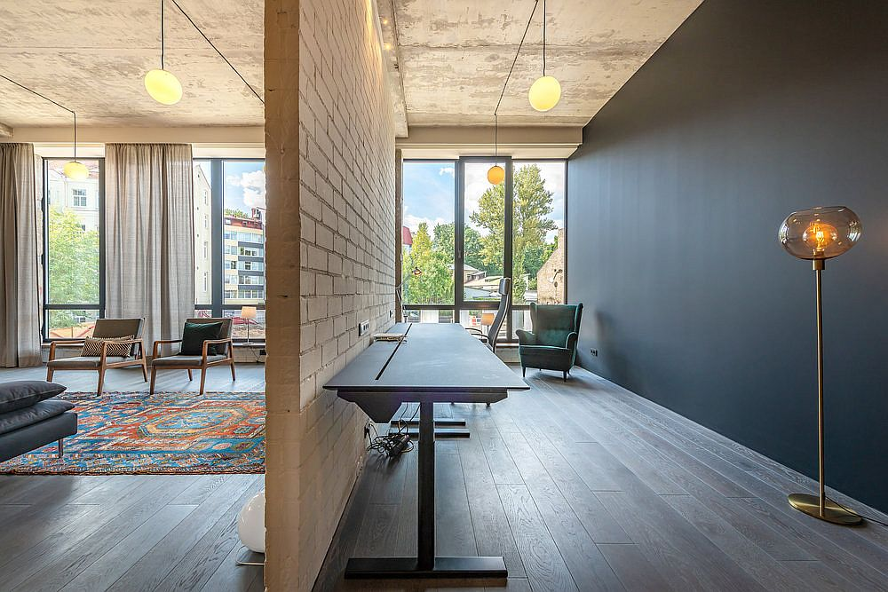 Workspace with polished dark gray walls adds modernity to the industrial apartment that was once a warehouse
