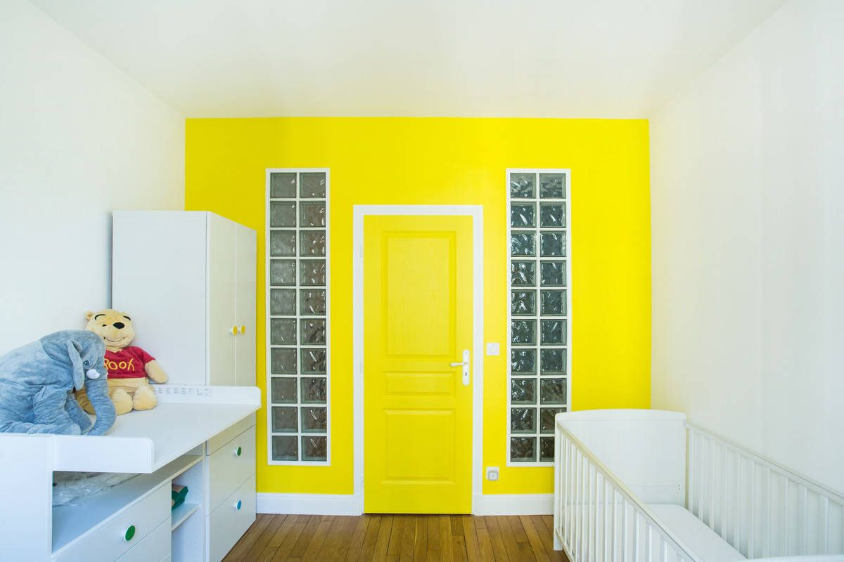 Yellow accent wall and door create a stunning visual focal point in this contemporary Paris nursery