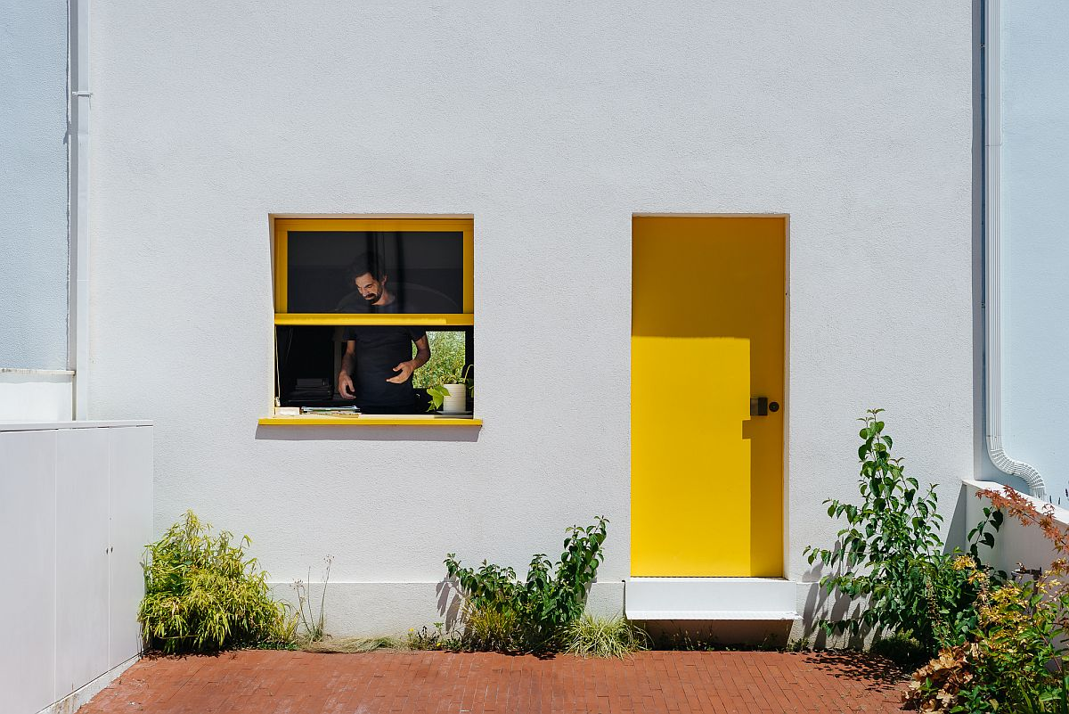Yellow-doors-and-window-frames-bring-color-to-the-exterior-of-the-house-in-white-60862