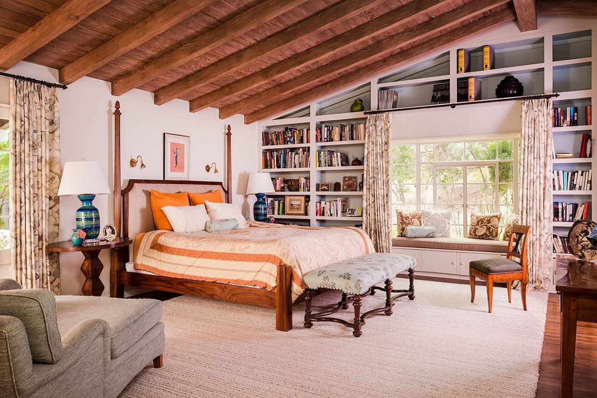 Accent pillows add orange to the spacious bedroom with traditional style