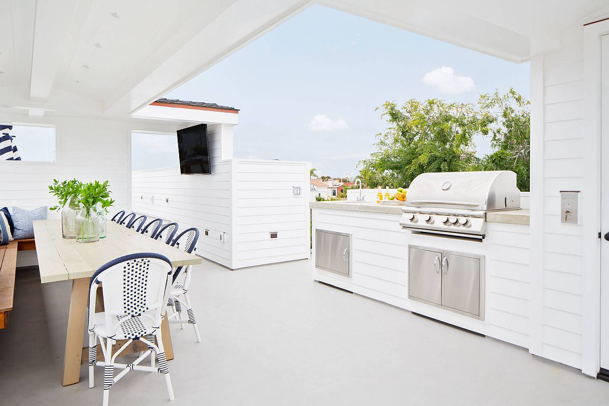 Awesome-rooftop-outdoor-kitchen-with-a-cheerful-beach-style-and-a-covered-dining-space-next-to-it-45711