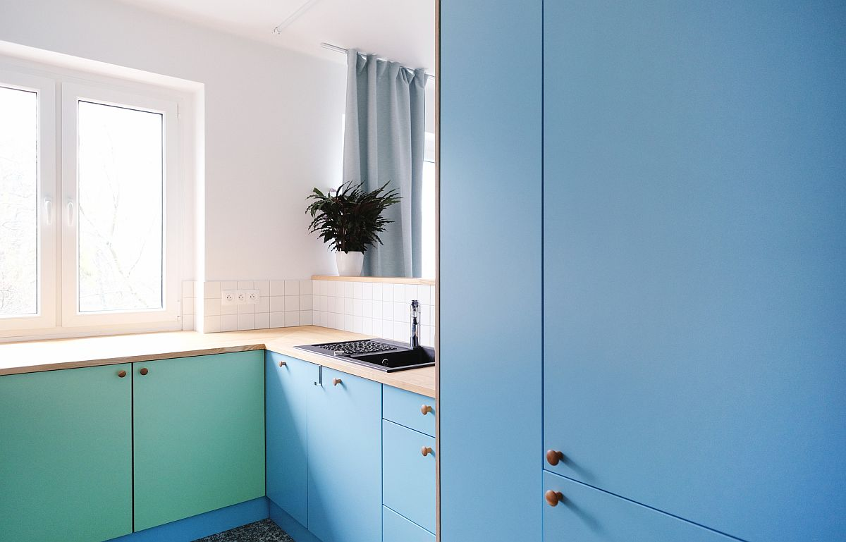 Blue and sea green cabinets add color to the adaptable kitchen of the apartment in white