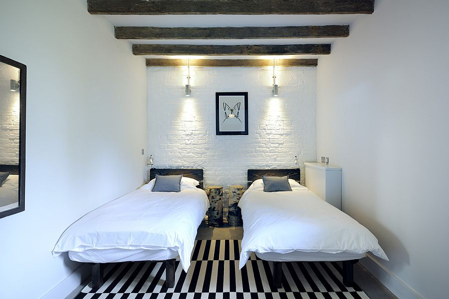 Brick wall painted white fits in with the contemporary style of the small bedroom