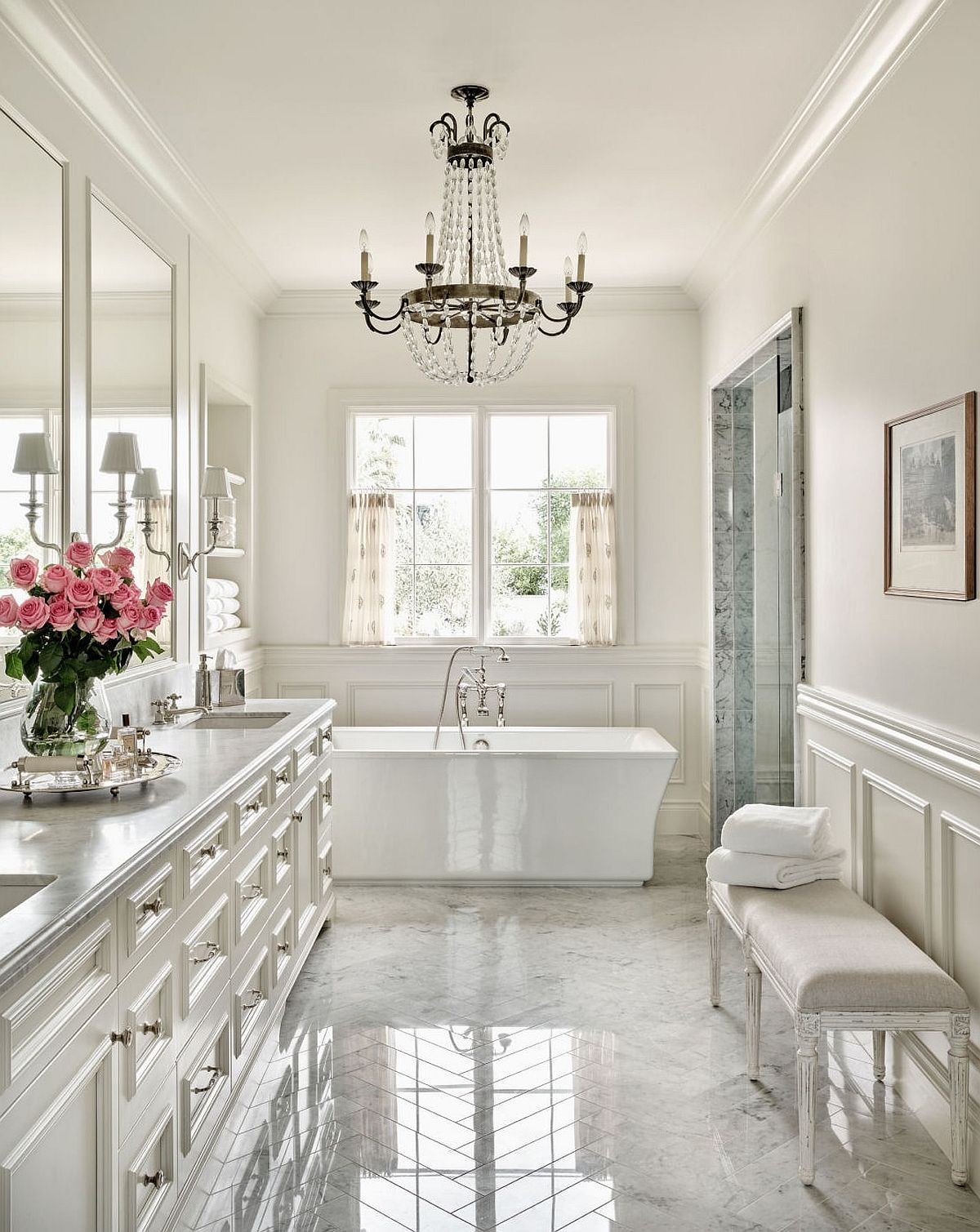 Classic bathroom in white with a beautiful black chandelier and a standalone white bathtub