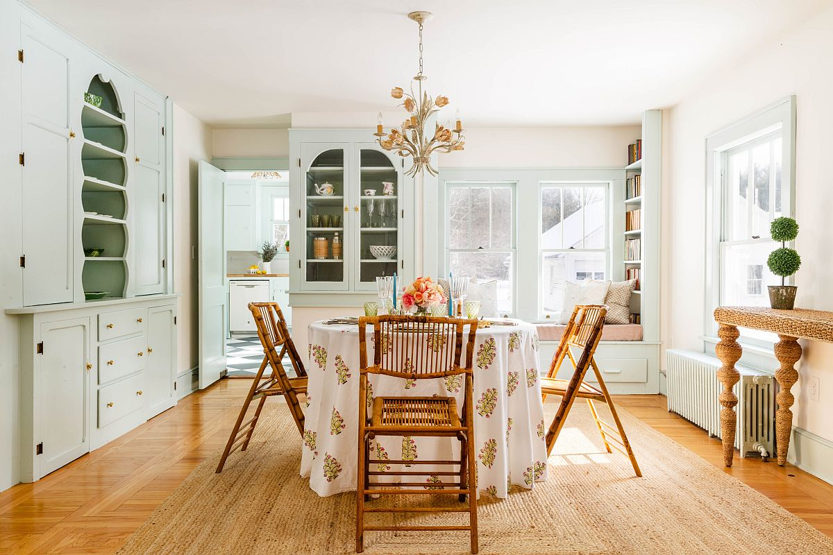 Classy shabby chic dining space with a round dining table and ample shelving in the backdrop