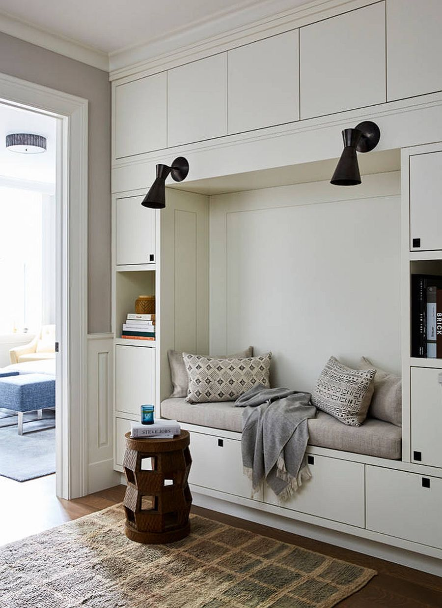 Collection of closed cabinet and open shelves creates space for storage and books in this bedroom