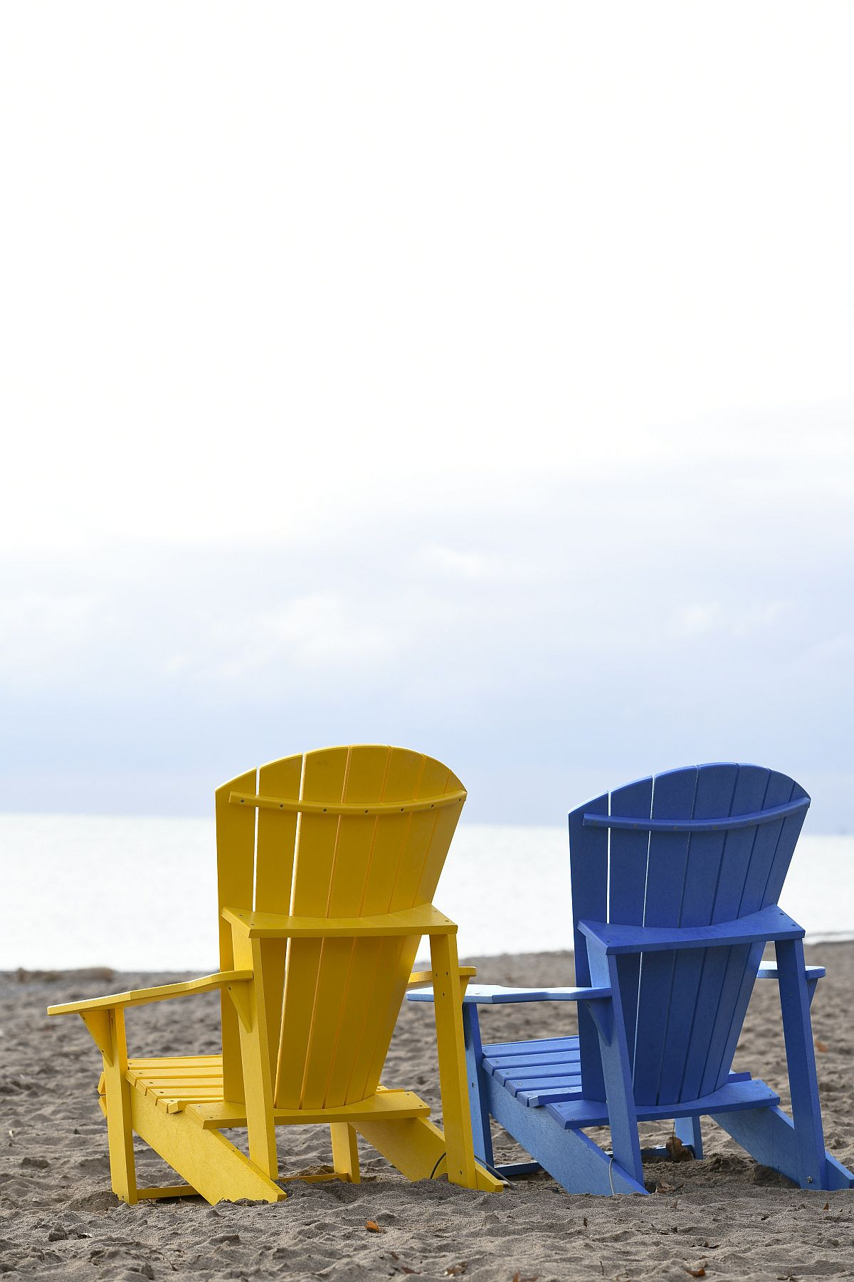Colorful wooden chairs on the beach offer lovely views of the waves and beyond