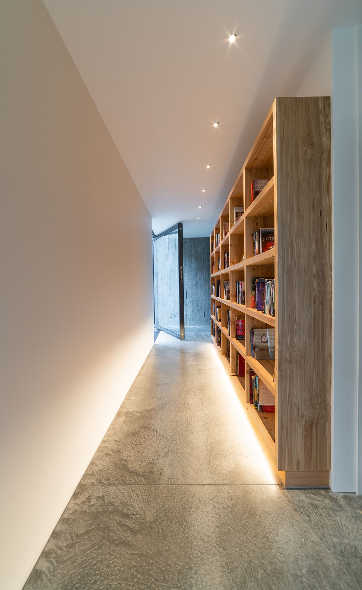 Custom wooden bookshelf in the hallway adds something different to the modern home