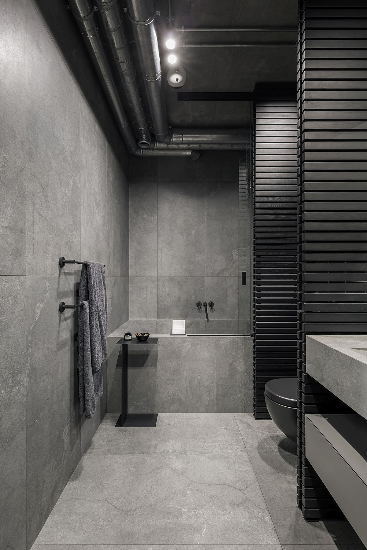 Dark gray and black contemporary bathroom with exposed duct pipes and naural stone