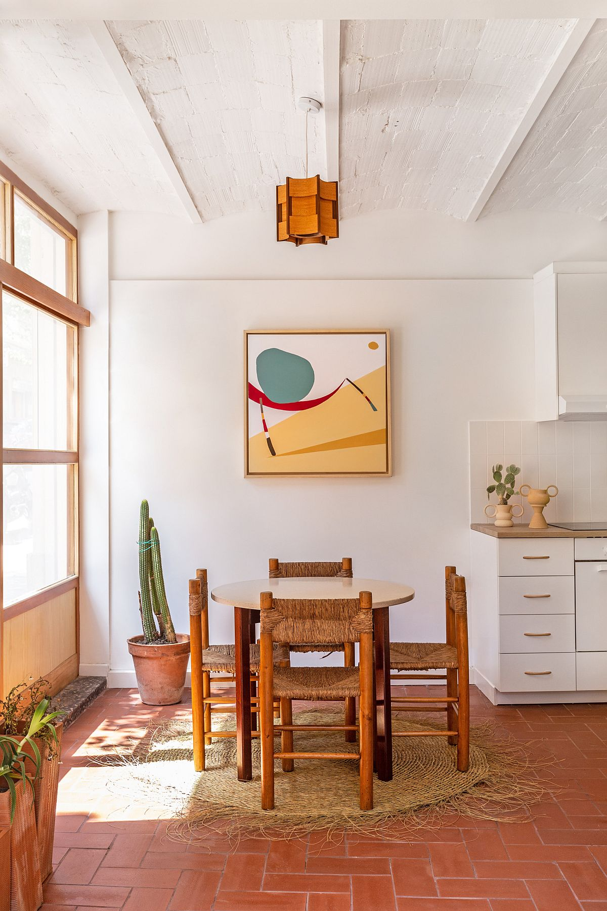 Delightful little dining room with terracotta floor tiles veers more towards modern than Mediterranean