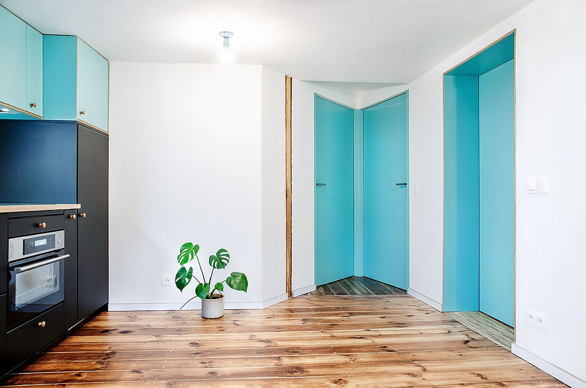 Doors and a couple of kitchen cabinet add blue to the attic apartment in white and wood