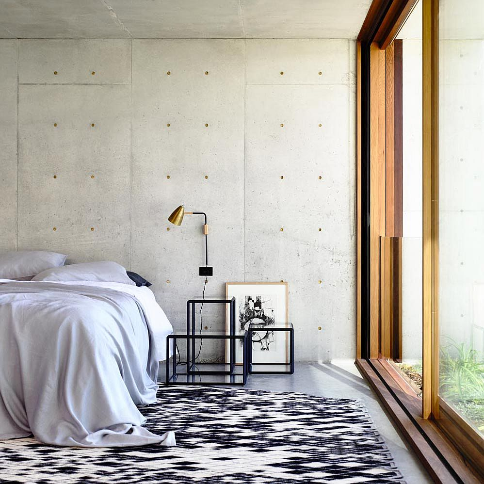 Exposed concrete walls create a modern minimal backdrop in the bedroom with sliding glass doors