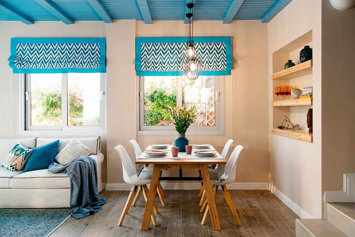 Eye-catching blue ceiling steals the show in this modest modern Mediterranean dining space