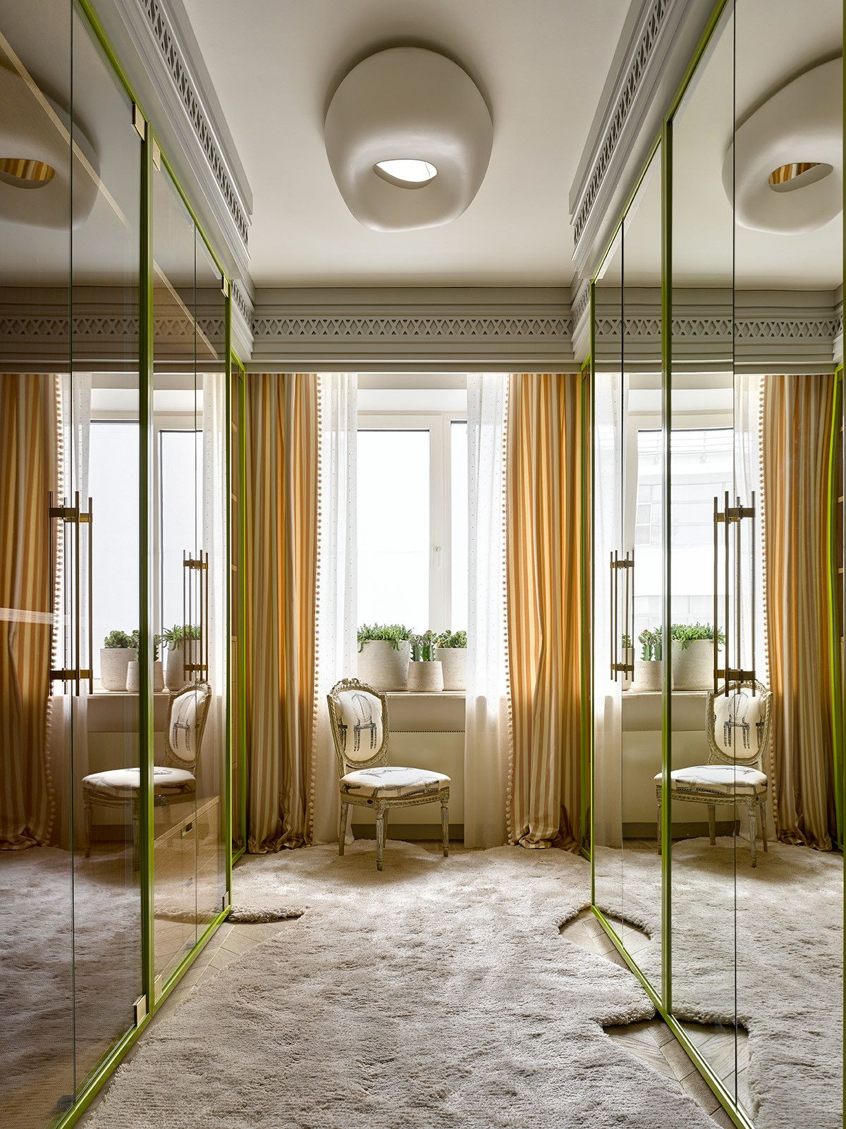 Fabulous carpeted walk-in closet with mirrored wardrobe doors and a tinge of green