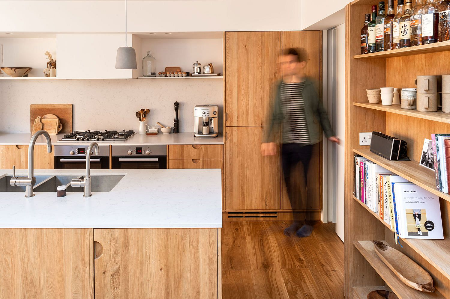 Floating shelves and closed cabinets combine to shape an efficient modern kitchen in white and wood