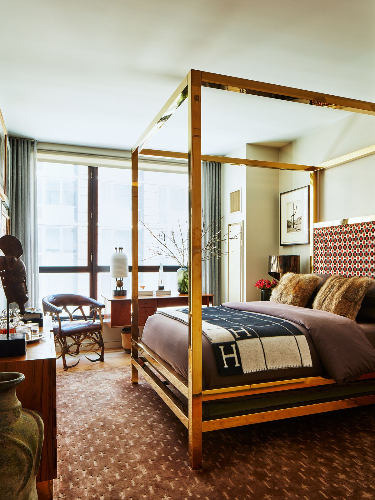 Four-poster bed with a golden metallic frame makes a statement inside this modern eclectic bedroom