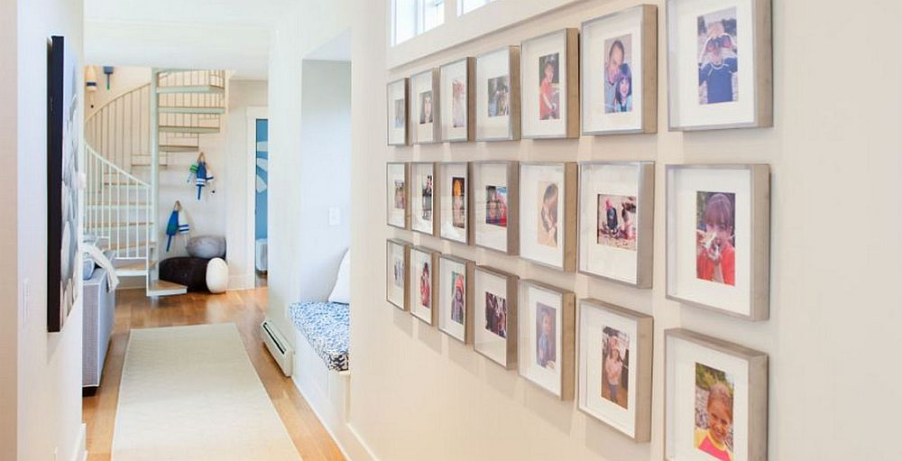 Framed personal photographs used to decorate the white becah style hallway