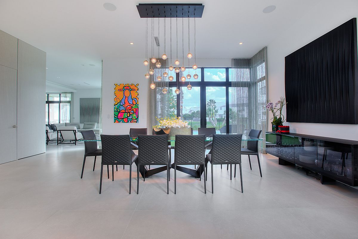 Gorgeou minimal dining room with colorful wall art piece in the backdrop and cascading chandelier