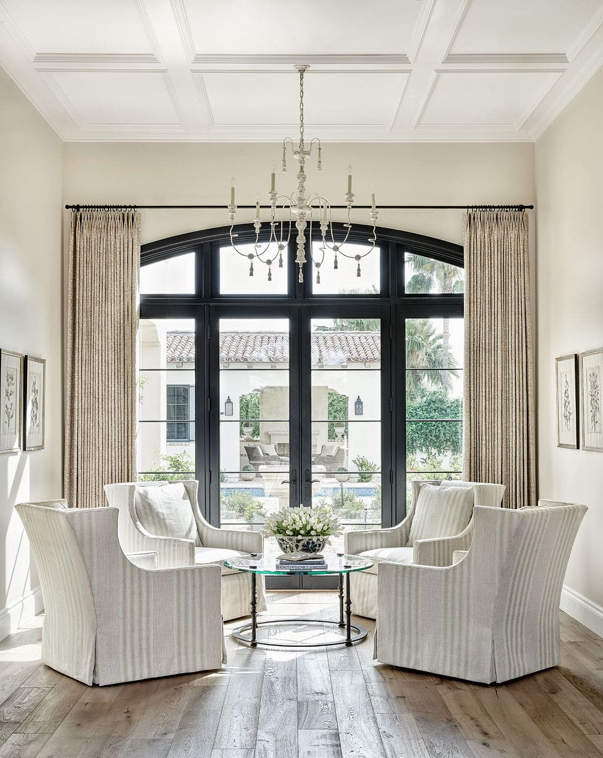 Gorgeous sitting room in white with ample natural light and a window that shapes the backdrop