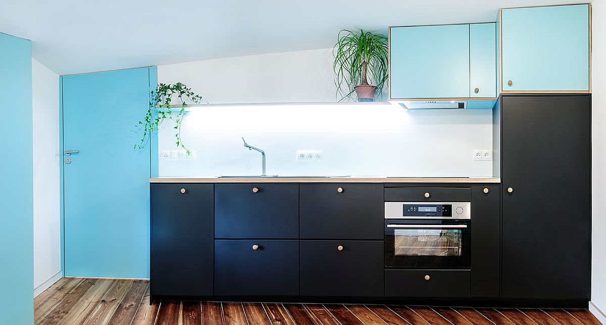 Kitchen with dark cabinets and splashes of blue is perfect for the modest attic flat and studio