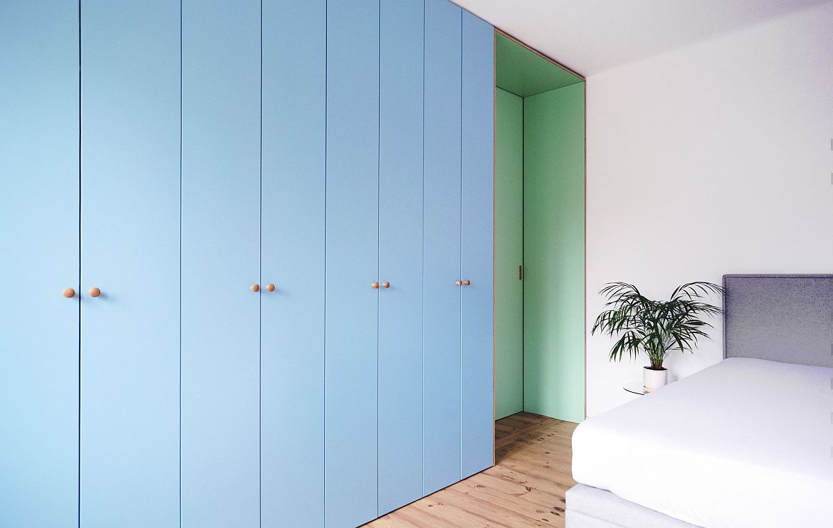 Light blue cabinets coupled with sea green sliding door inside the bedroom