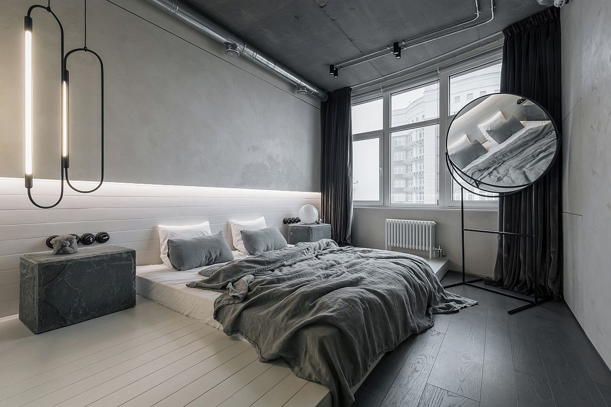 Modern industrial bedroom has a monochromatic black and white look along with innovaive lighting
