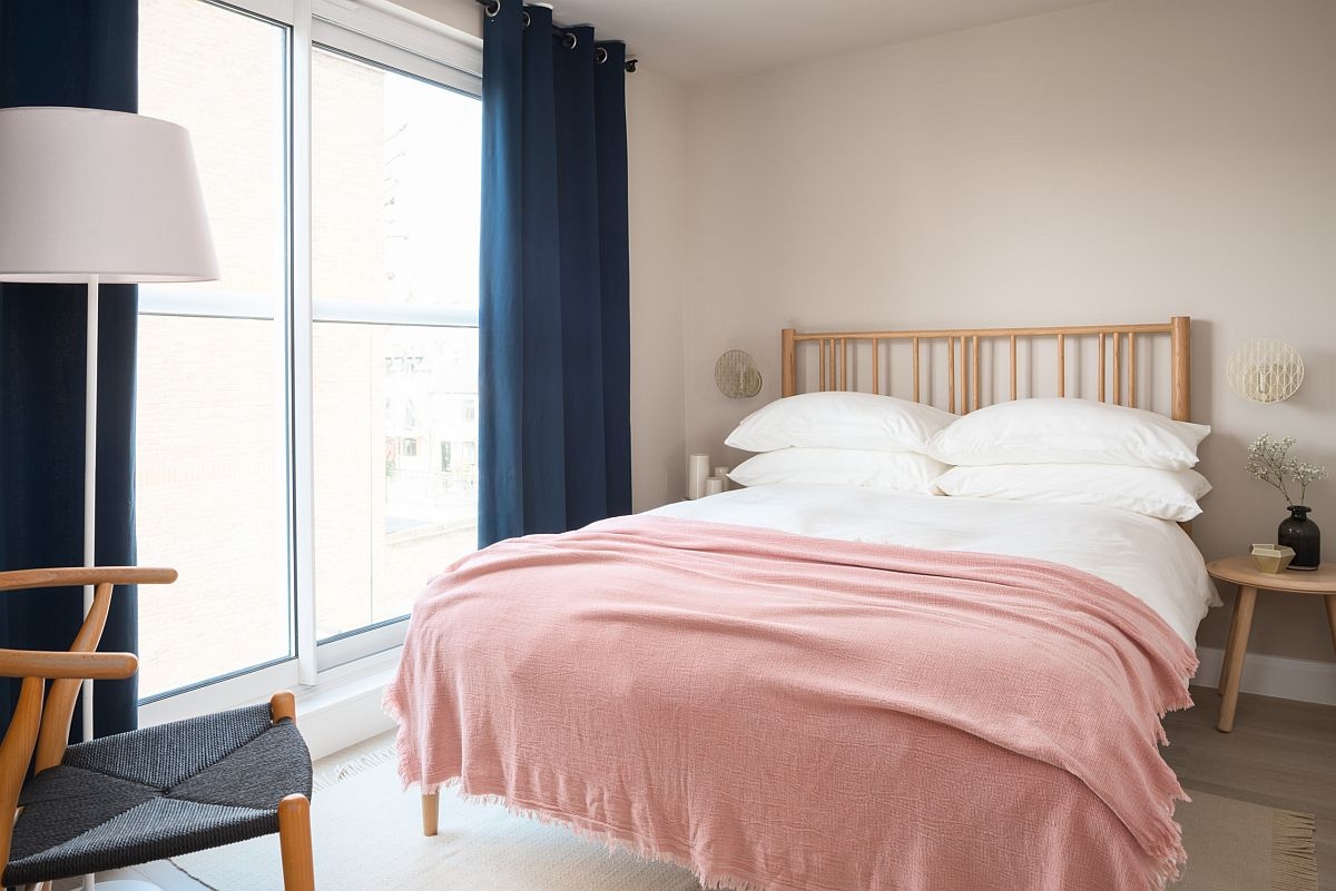 Navy blue drapes and pink bed sheets usher color into this Scandinavian style bedroom