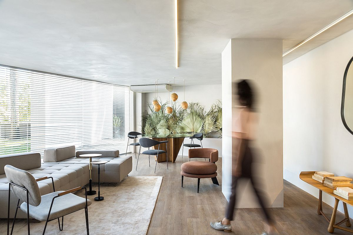 Open plan living area of the apartment with dining space that features a display of dried palm leaves