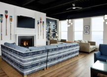 Paddles-on-the-wall-striped-couch-in-blue-and-white-and-a-cozy-fireplace-shape-the-interior-of-the-beach-club-lounge-27863-217x155
