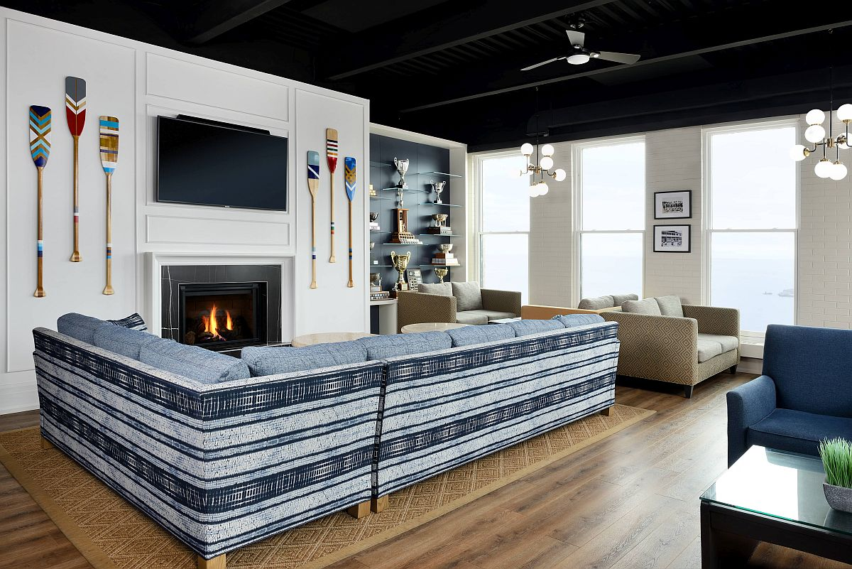 Paddles on the wall, striped couch in blue and white and a cozy fireplace shape the interior of the beach club lounge