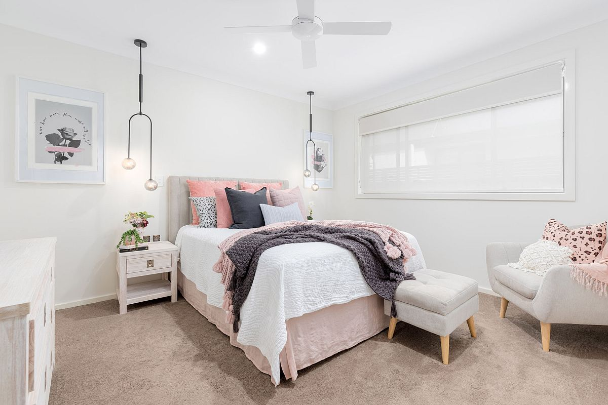 Pillows and accents bring pops of light pink to this Scandinavian style bedroom