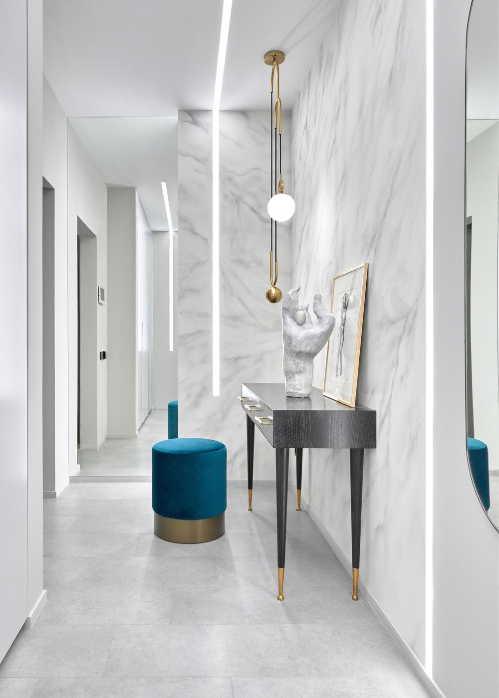 Polished and minimal contemporary hallway of Moscow apartment with a splash of blue thrown into the mix