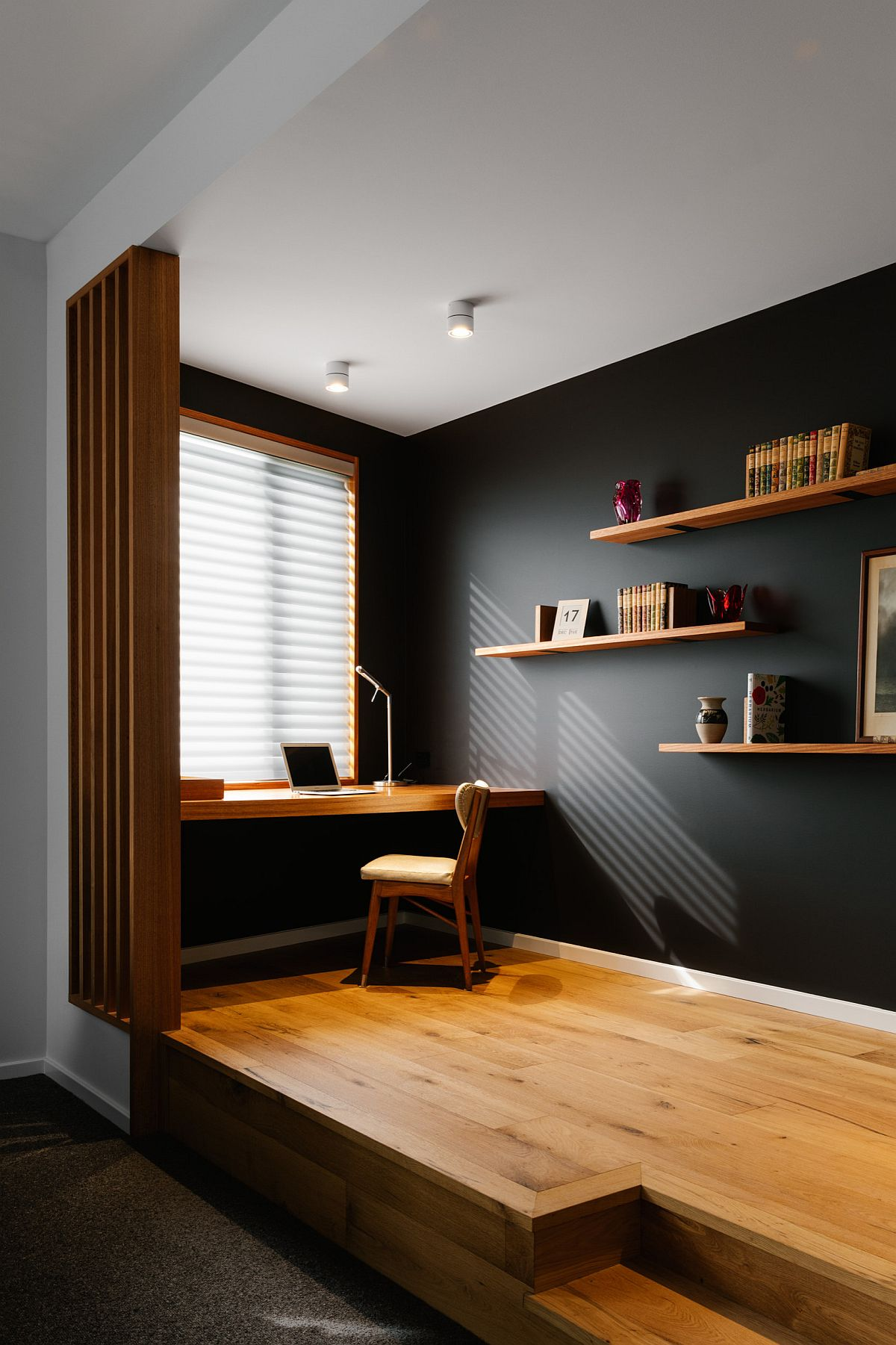 Raised wooden floor delineates this black and wood home office from the living area