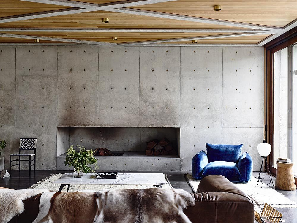 Raw concrete walls in the living room along with wooden ceiling usher in ample textural contrast