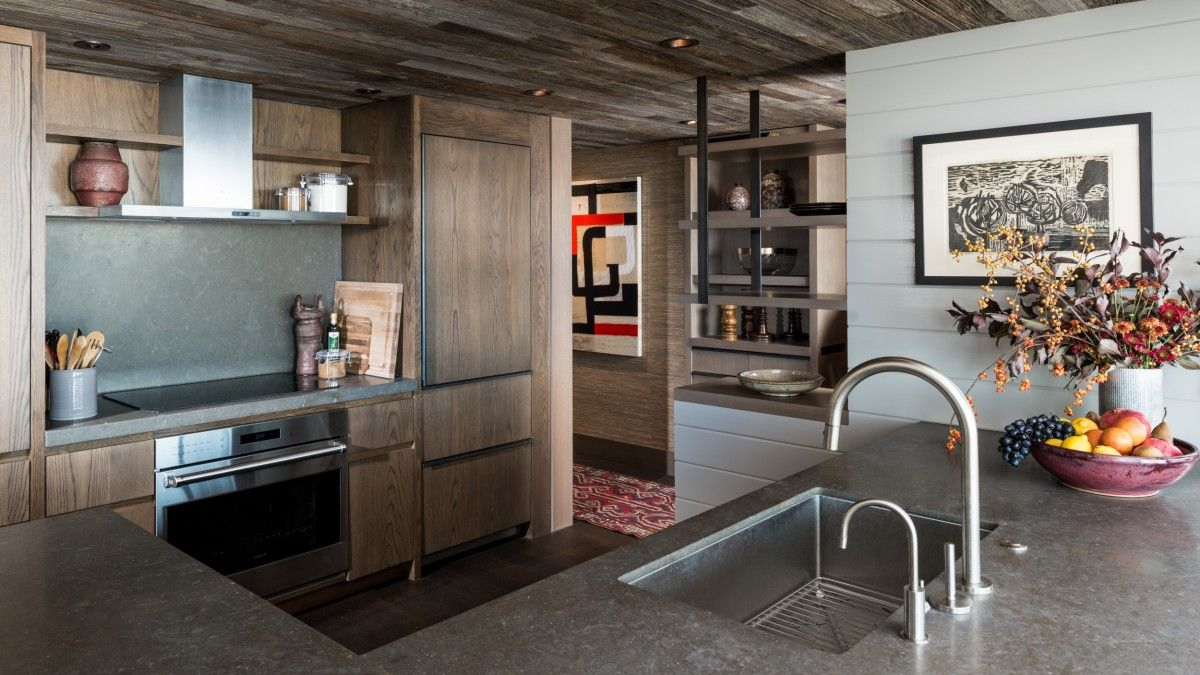 Reclaimed wooden ceiling coupled with wooden cabinets in the cozy modern eclectic kitchen