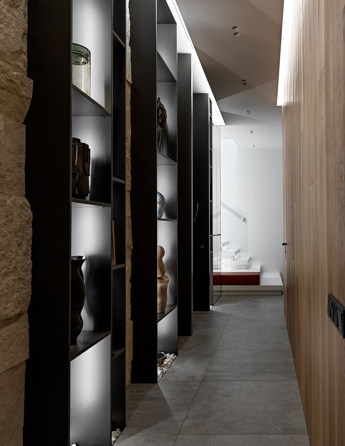 Series of brilliantly illuminated shelves create a stunning display in this unique hallway