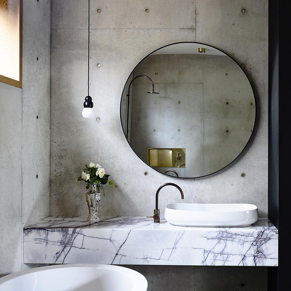 Slim marble vanity in the concrete bathroom creates visual contrast inside the small space