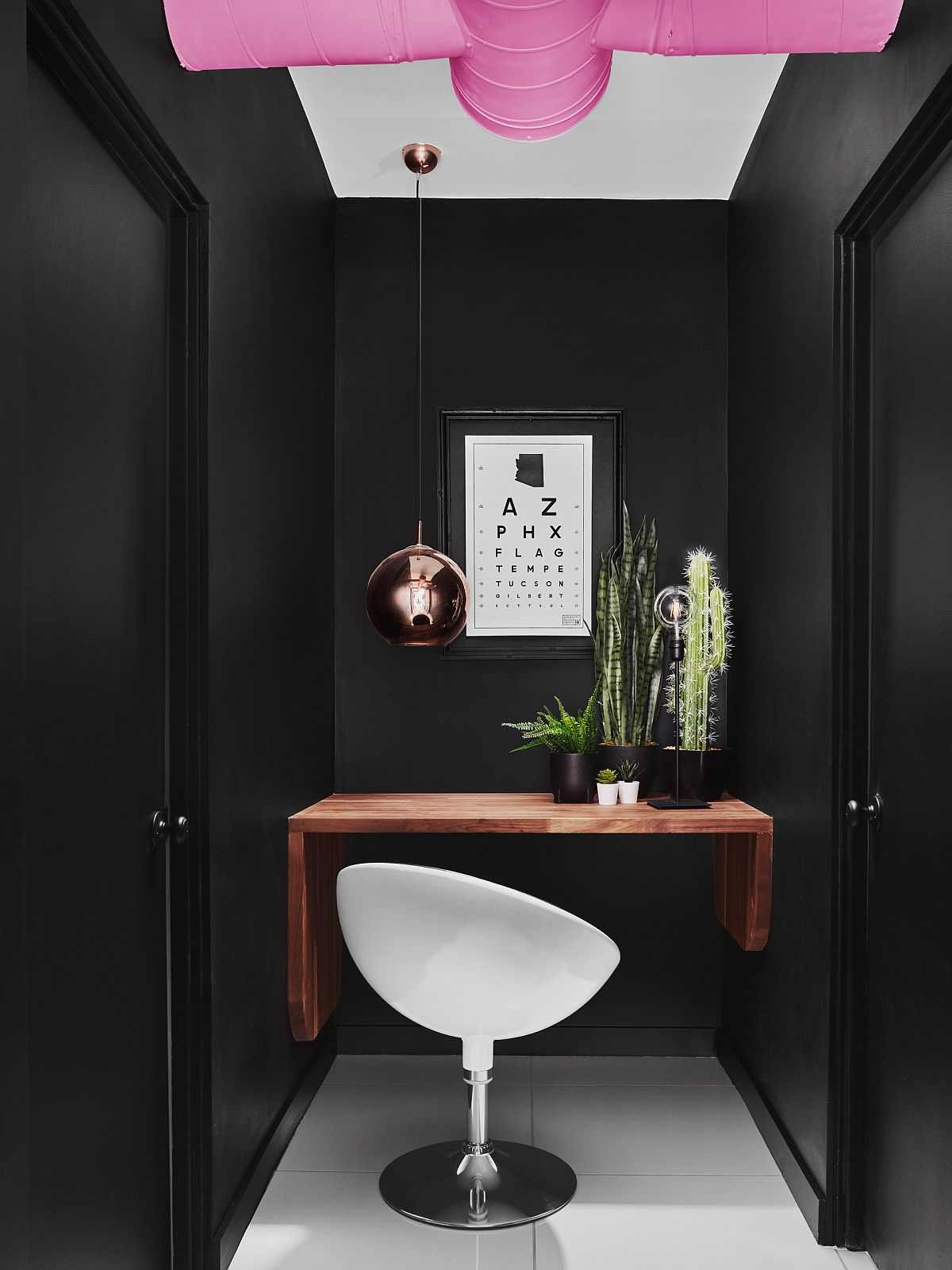 Small black home office with built-in wooden desk and copper pendant light