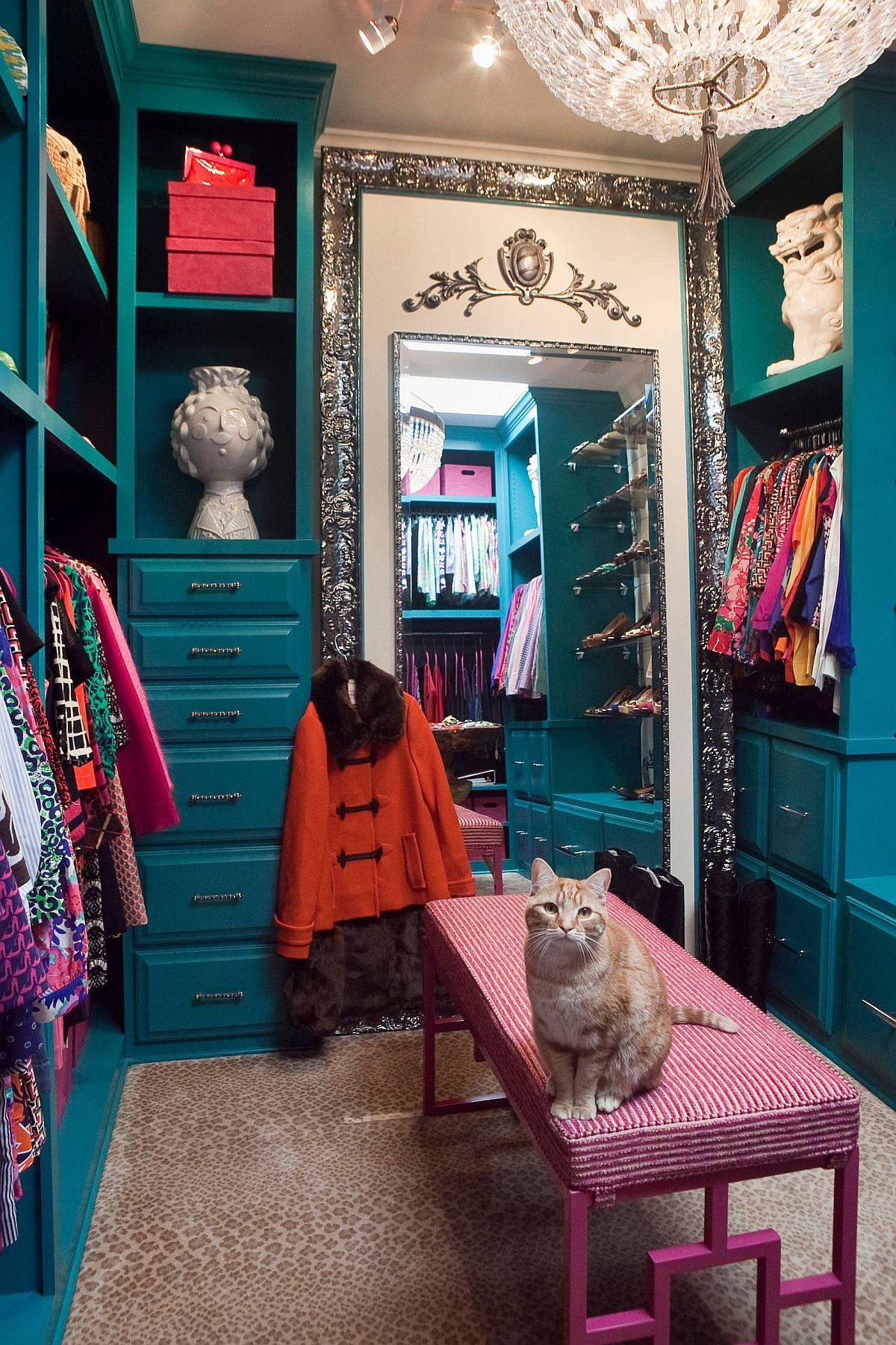 Small eclectic women's carpeted dressing room with blue cabinets and a painted pink desk
