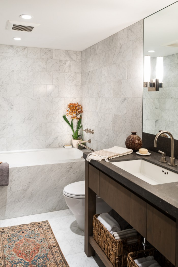 Small rug and the custom wooden vanity add textural contrast to the modern bathroom in white