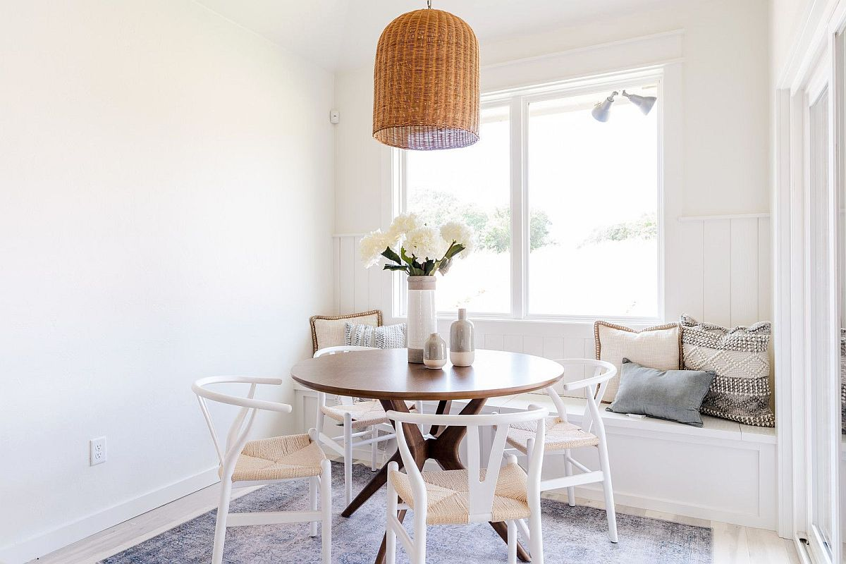 Small-white-dining-room-with-round-dining-table-chairs-and-a-comfy-window-seat-in-the-backdrop-40803