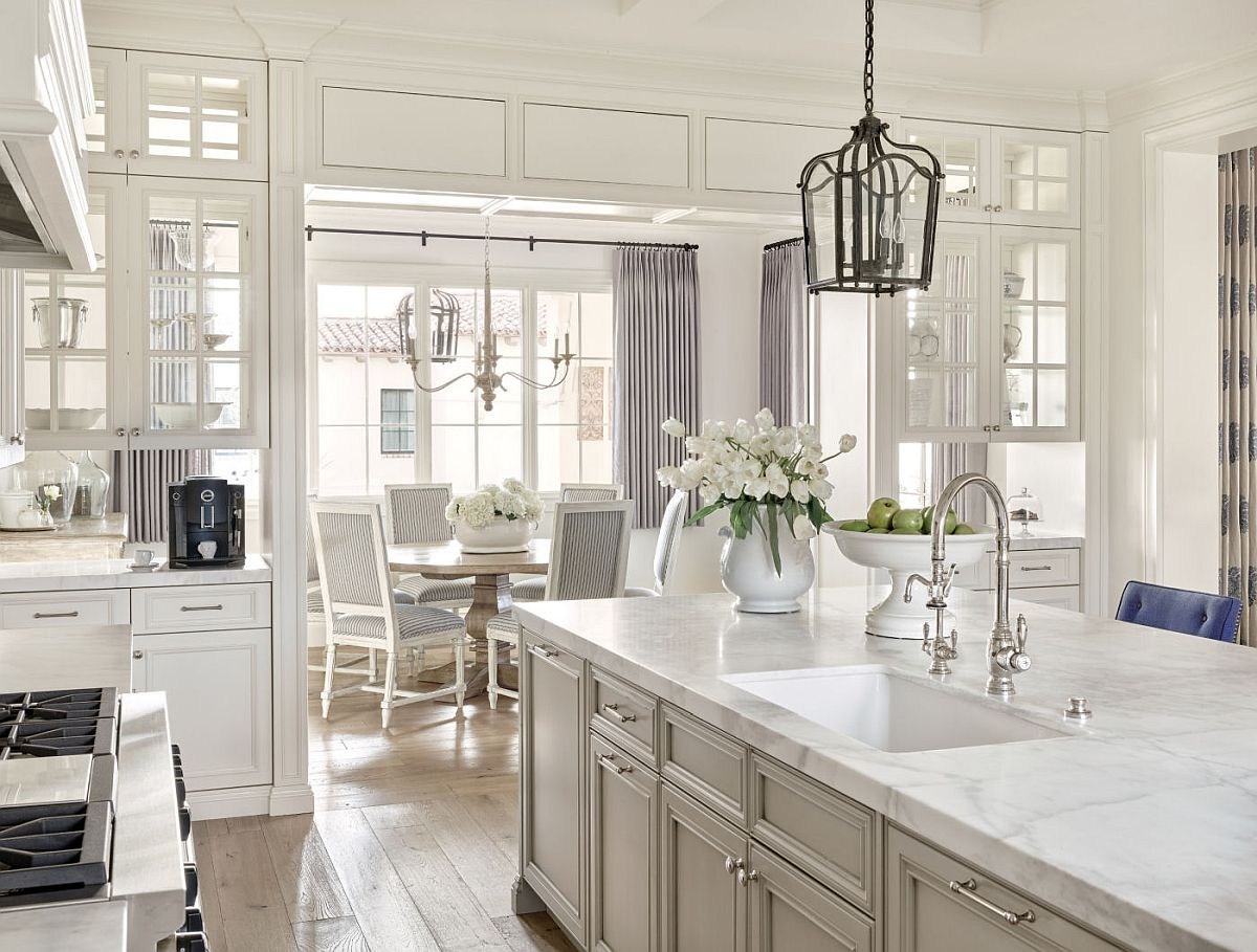 Traditional kitchen and dining are aof the remodeled home in white with gray accents and drapes
