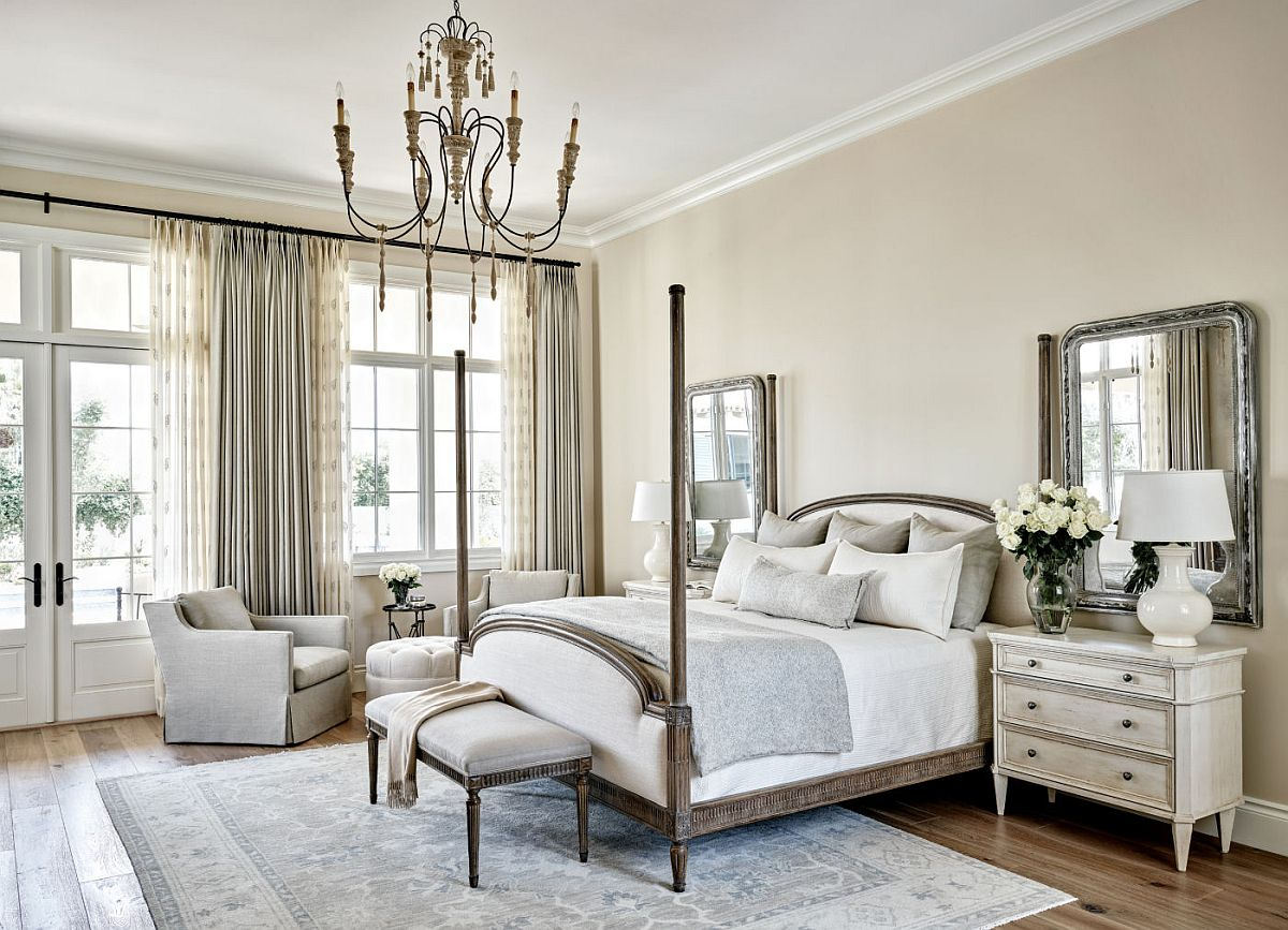 Transitional bedroom in white with mirrors above the nightstand that bring symmetry to the interior